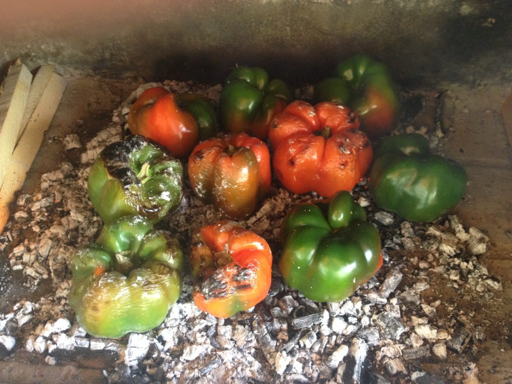 Peppers being cooked over embers