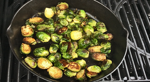 Showing how to infuse cherry wood smoke into brussels sprouts using an iron skillet on the gas grill is simple and easy and adds a smoky touch