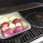 Onions on the grill with wood chunk over the flavor bar