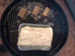 Our Pork Belly on the charcoal grill for our homemade smoked bacon